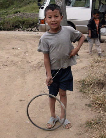 Bhutanese boy playing with tire